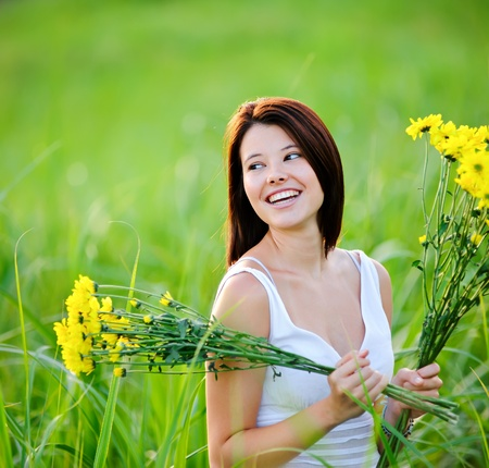 Adorable girl with flowers poses in a field during summer afternoon. Stock Photo - 8726325