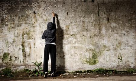 Joven con pintura en aerosol y una pared vacía de graffiti Foto de archivo