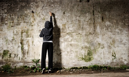 graffiti: Joven con pintura en aerosol y una pared vac�a de graffiti