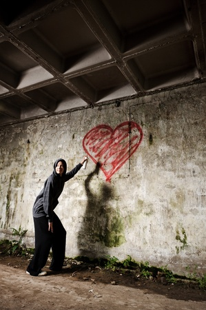 Graffiti artist paints a love valentine heart on grunge wall Stock Photo - 8726288