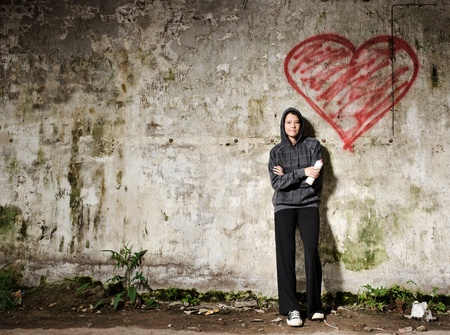 Proud graffiti girl stands with her valentine heart photo