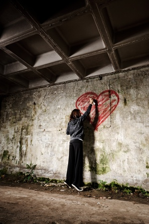 Graffiti artist paints a love valentine heart on grunge wall photo