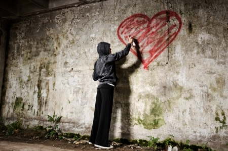 liefde: Graffitikunstenaar schildert een liefde valentine hart op grunge muur