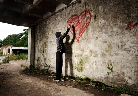 Artista de Graffiti pinta un corazón de San Valentín de amor en la pared de grunge