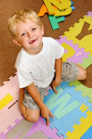 young blonde boy points to the new letter he has learned from the alphabet.