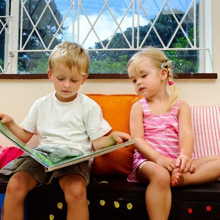 brat: Dziewczynka nasÅ'uchuje jej big brother czyta książkÄ™ nocujÄ… w szkole Zdjęcie Seryjne