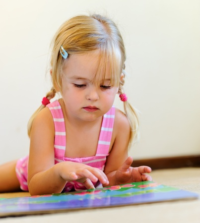 young adorable blonde girl reads a book on her own photo