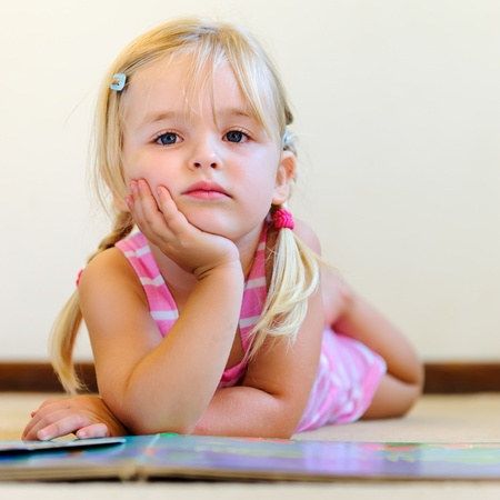 literate: cute young blonde girl thinks about the book she is reading at preschool  Stock Photo