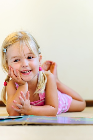 cute blonde girl with pigtails laughs and reads a book at kindergarten photo