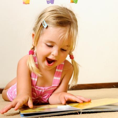 ni�os leyendo: ni�a rubia adorable Lee un libro sobre su propia