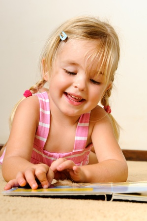 lying down on floor: young adorable blonde girl reads a book on her own Stock Photo