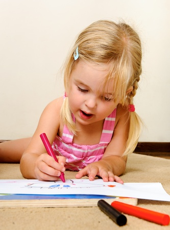 crayon drawing: blonde girl drawing with crayons in school