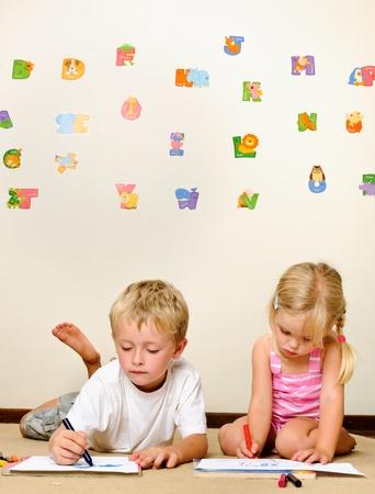 dessin enfants: deux enfants heureux adorables dessin avec crayons � la pr�maternelle Banque d'images