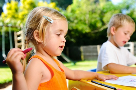 cute adorable young kids with crayons at an outside playschool photo