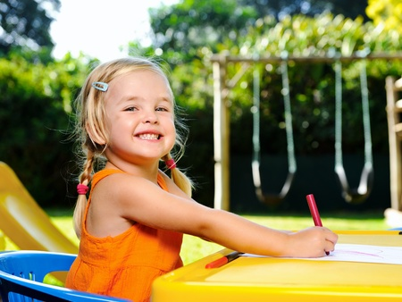 cute blonde girl with pigtails smiles with joy while drawing with crayons at kindergarten photo
