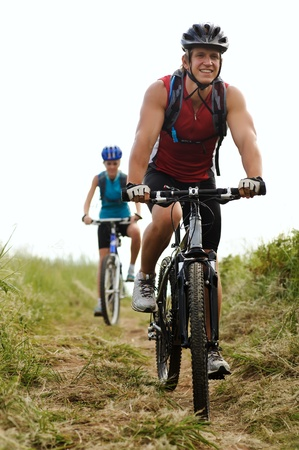 Happy couple riding bicycles outside, healthy lifestyle fun concept photo