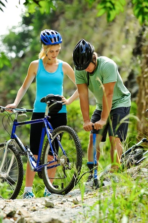 flat tyre: Couple have a flat tyre with mountain bike outdoor in the wilderness Stock Photo