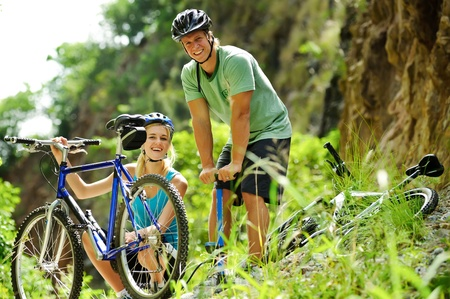 Cute adorable couple smile and are happy with mountain bike outdoors Stock Photo - 8929994