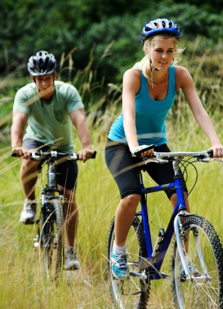 cycling   helmet: Happy couple riding bicycles outside, healthy lifestyle fun concept Stock Photo