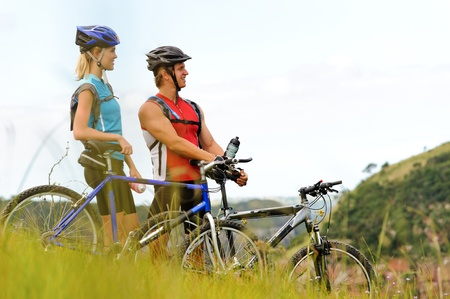 Happy mountainbike couple outdoors have fun together on a summer afternoon photo