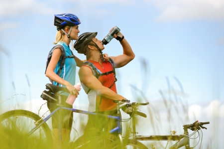 mountain bicycle: Attractive, healthy couple drink from their water bottles on mountain bikes. active outdoor lifestyle concept