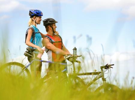 montando bicicleta: Bicicleta de monta�a feliz pareja al aire libre divertirse juntos en una tarde de verano Foto de archivo
