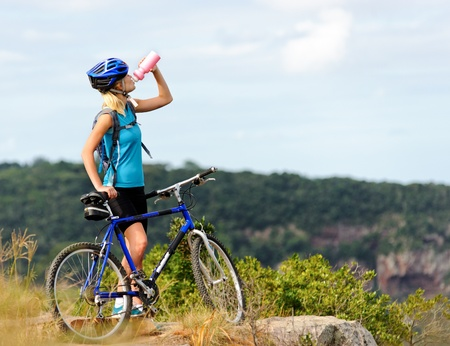 Attractive, healthy woman drinks from her water bottle on mountain bike. active outdoor lifestyle concept  Stock Photo