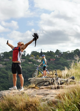happy free fun man stands victorious on a mountain with arms outstretched and helmet in hand photo