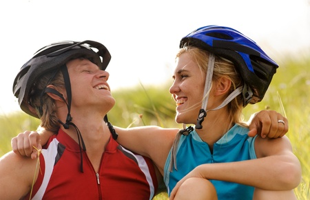 Cute couple with cycling helmets laugh together and have fun outdoors photo