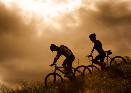 silhouette couple mountainbike riding outdoors at sunset photo