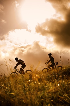 bicycle silhouette: silhouette couple mountainbike riding outdoors at sunset