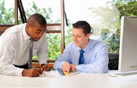 mentors: African businessman mentors his white associate on how to choose colours appropriately with colour tags  Stock Photo