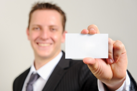 Ambitious white man in business suit smiles confidently and holds out his business card; selective focus on card  photo