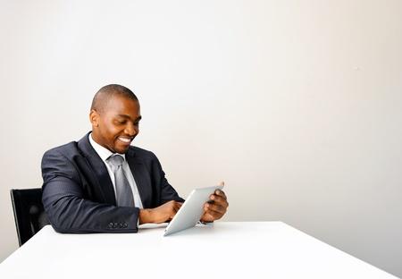 updated: Joven africana profesional utiliza una tableta para mantenerse actualizado con el mercado