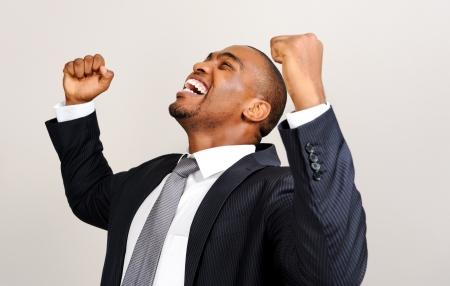 Attractive black professional raises his fists in joy and triumph photo