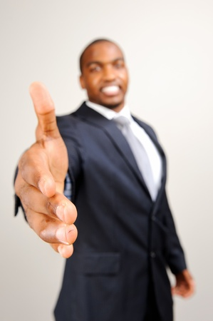 Black man in formal suit extends his hand out for a handshake, selective focus on hand photo