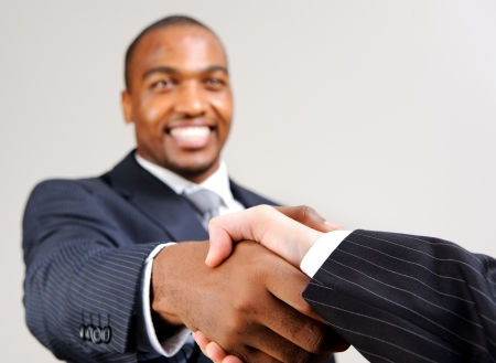 Black man in formal suit shakes the hand of an unknown caucasian man  photo