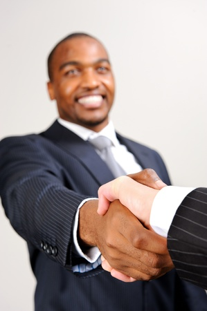 black handshake: Black man in formal suit shakes the hand of an unknown caucasian man  Stock Photo