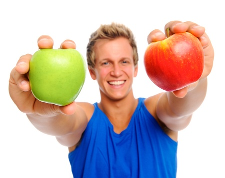 approachable: Smiling man holding two apples in front of him; healthy living concept