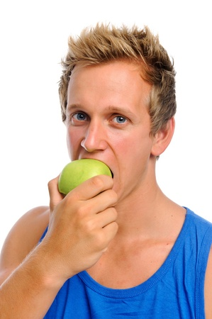 Handsome caucasian man biting into a green apple isolated on white photo