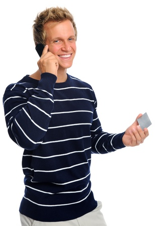 Happy blonde man on his mobile phone holding his credit card; e-commerce concept Stock Photo - 9967936