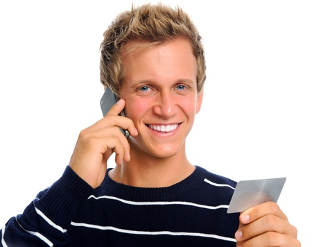 Happy blonde man on his mobile phone holding his credit card; e-commerce concept Stock Photo - 9967943