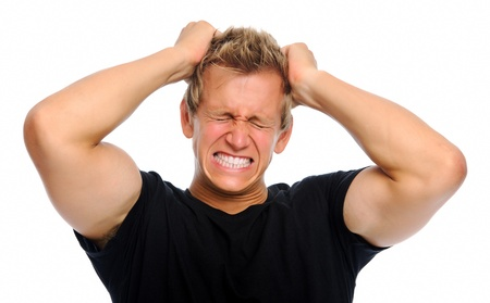 outrage: Young man clenching his teeth, pulling his hair, suffering from stress