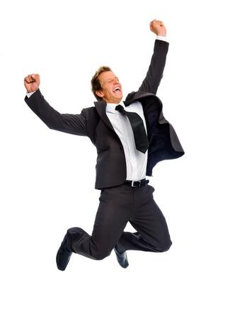 Hombre entusiasmado en traje de negocios salta en Victoria y alegría, aislado en blanco Foto de archivo