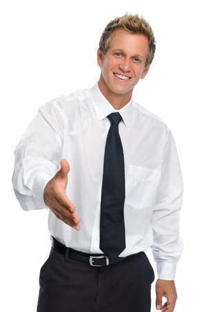 assured: Man in business attire offers a handshake isolated on white