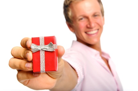 Happy blonde man holding a present for valentines day; selective focus on box photo