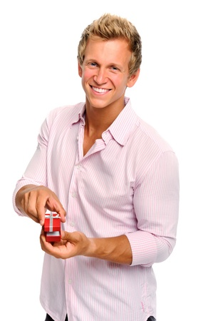 Happy blonde man holding a present for valentines day  photo