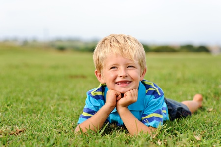 lying on grass: A blond child lies on some grass on a summer day