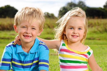 sibling: Two blond children pose for a portrait in a field  Stock Photo