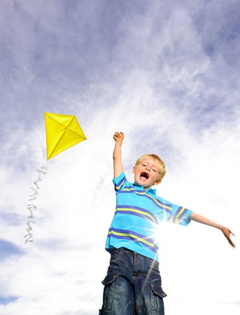 analogy: Young boy flies his yellow kite on a sunny day; a pictorial analogy for ambition